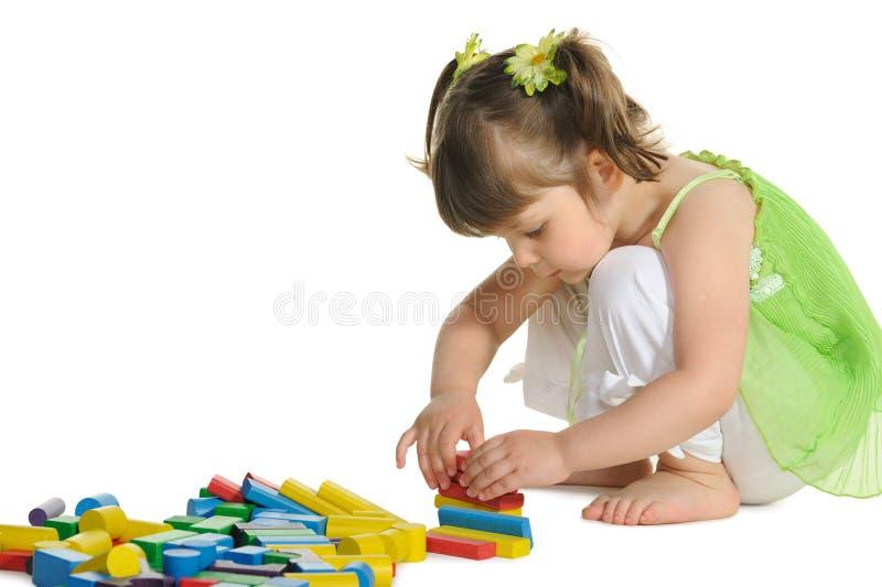 Το καλό μικρό κορίτσι παίζει τους ξύλινους κύβους χρώματος στοκ φωτογραφίες