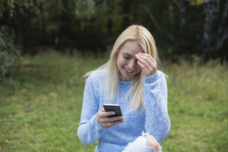 Το καλό χαμογελώντας κορίτσι διαβάζει sms στο κινητό τηλέφωνο, στοκ φωτογραφία με δικαίωμα ελεύθερης χρήσης
