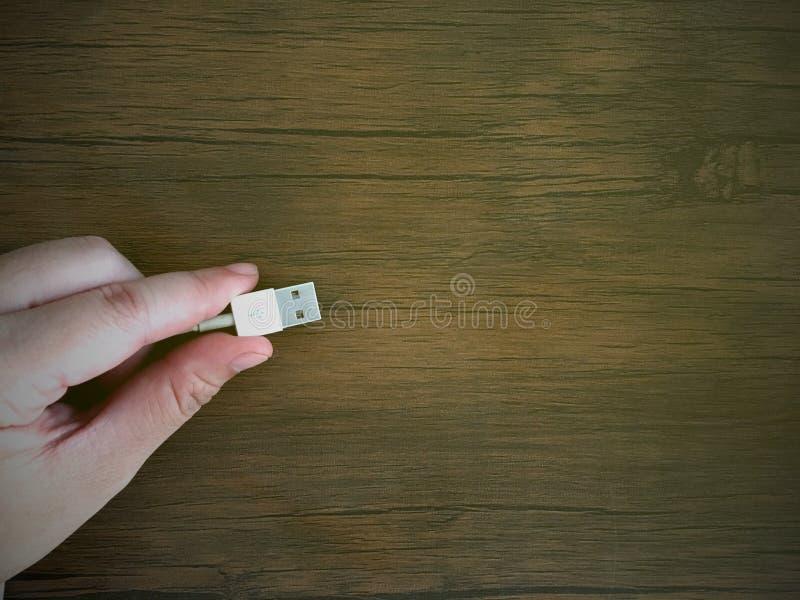 Το καλώδιο εκμετάλλευσης USB χεριών γυναικών για συνδέει με το ηλεκτρονικό μέρος στον ξύλινο πίνακα στοκ φωτογραφία με δικαίωμα ελεύθερης χρήσης
