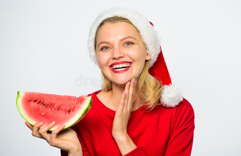 Το καπέλο santa ένδυσης κοριτσιών τρώει το άσπρο υπόβαθρο καρπουζιών φετών Το καλοκαίρι μεταχειρίζεται στη γιορτή Χριστουγέννων Ε στοκ εικόνα