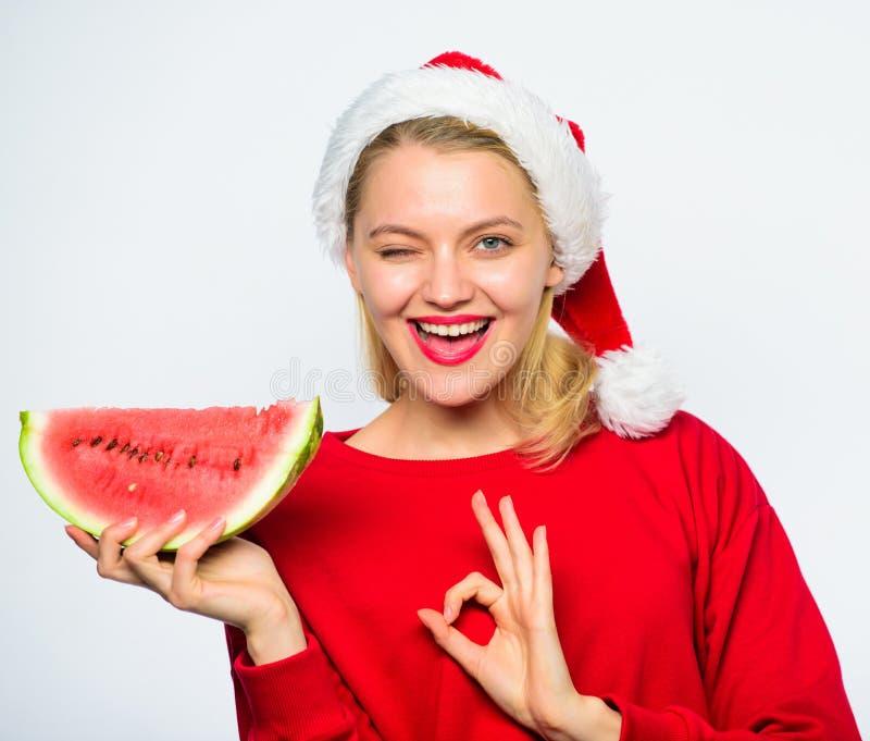 Το καπέλο santa ένδυσης κοριτσιών τρώει το άσπρο υπόβαθρο καρπουζιών φετών Το καλοκαίρι μεταχειρίζεται στη γιορτή Χριστουγέννων Ε στοκ φωτογραφία με δικαίωμα ελεύθερης χρήσης
