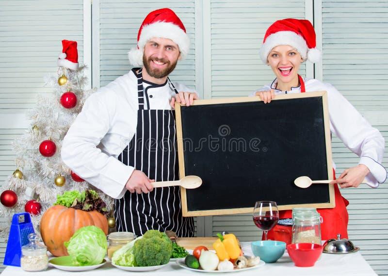 Το καπέλο santa αρχιμαγείρων ανδρών και γυναικών κοντά στο χριστουγεννιάτικο δέντρο κρατά το διάστημα αντιγράφων πινάκων Οικογενε στοκ φωτογραφίες