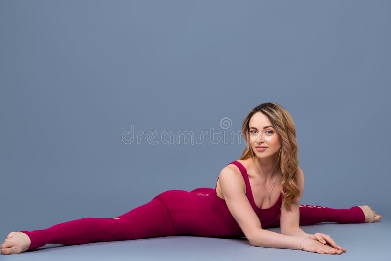 Το κατάλληλο φίλαθλο κορίτσι τεντώνει Νέα όμορφη gymnast γυναίκα σε ένα jumpsuit που κάνει τη διαγώνια διάσπαση, σπάγγος Ο αθλητι στοκ φωτογραφία