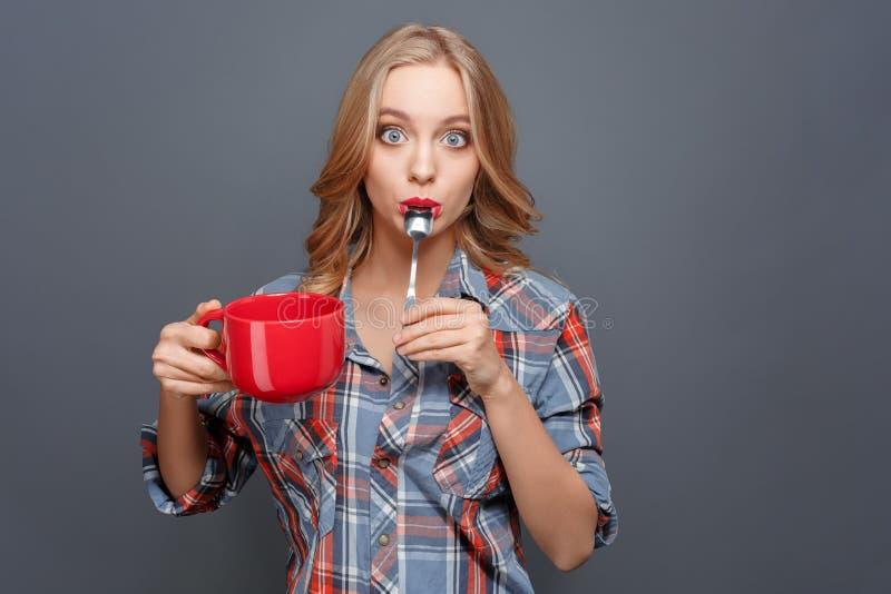 Το κατάπληκτο κορίτσι στέκεται και θέτει Κρατά ένα κόκκινο φλυτζάνι στο χέρι της και κρατά το μικρό κουτάλι στο στόμα της αυτή στοκ εικόνες με δικαίωμα ελεύθερης χρήσης