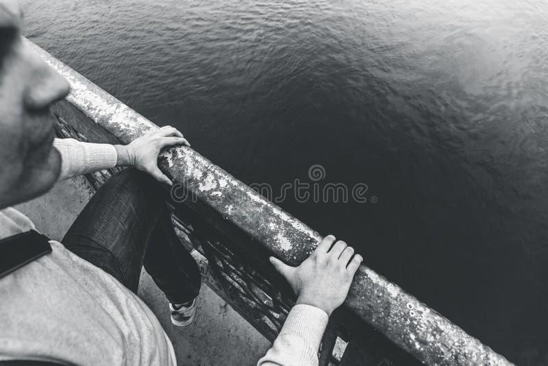 Το καταθλιπτικό άτομο αναρριχείται πέρα από το κιγκλίδωμα της γέφυρας για να πηδήσει και να δεσμεύσει την έννοια προβλημάτων αυτο στοκ εικόνα