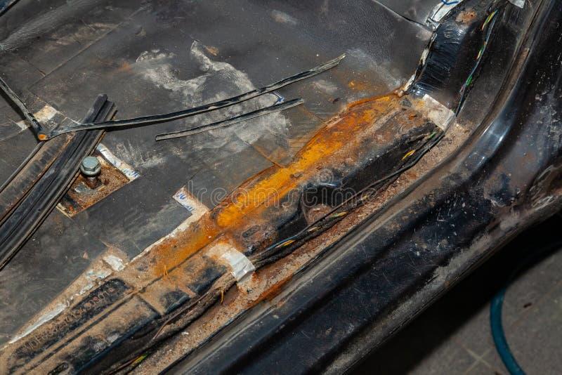 Το κατώτατο όριο και το πάτωμα του αυτοκινήτου με τη φωτεινή κόκκινη σκουριά και της διάβρωσης στην πλάτη του Μαύρου χρωματίζουν  στοκ εικόνες με δικαίωμα ελεύθερης χρήσης
