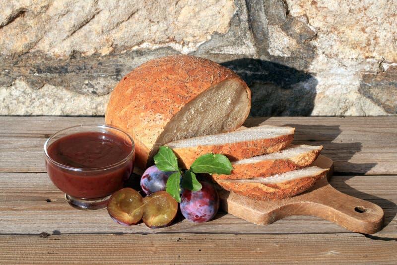 Το κατ' οίκον γίνοντα δαμάσκηνο φράσσει και το ψήσιμό σας γύρω από τη φραντζόλα του ψωμιού στοκ εικόνες