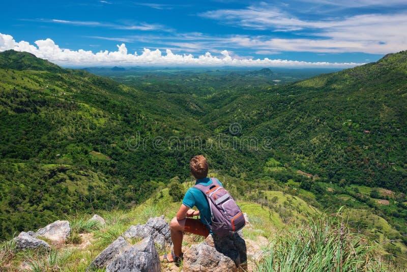 Το καυκάσιο άτομο οδοιπόρων παίρνει ένα υπόλοιπο στην αιχμή βουνών με το σακίδιο πλάτης στοκ φωτογραφίες