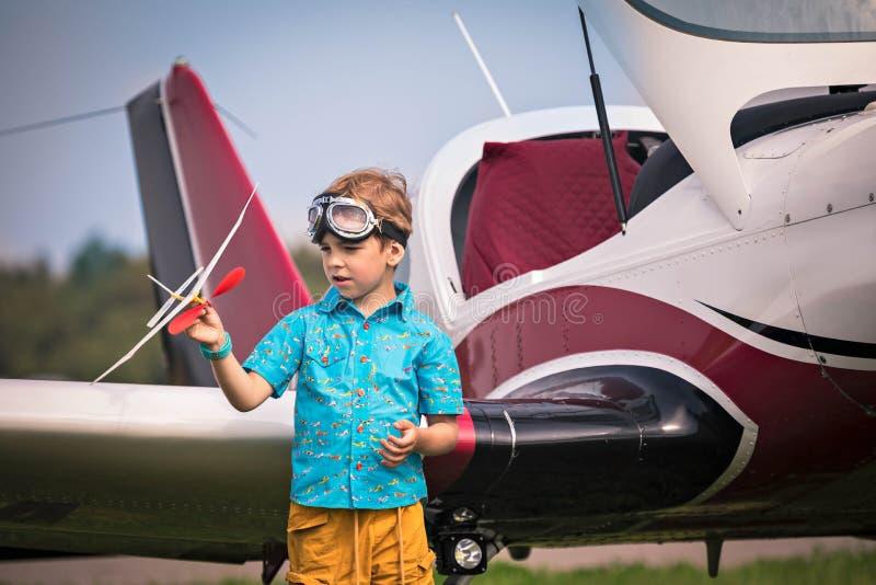 Το καυκάσιο αγόρι στα κίτρινα σορτς, ένα μπλε πουκάμισο και στα σημεία αεροπορίας κρατά το αεροπλάνο παιχνιδιών διαθέσιμο και το  στοκ εικόνες