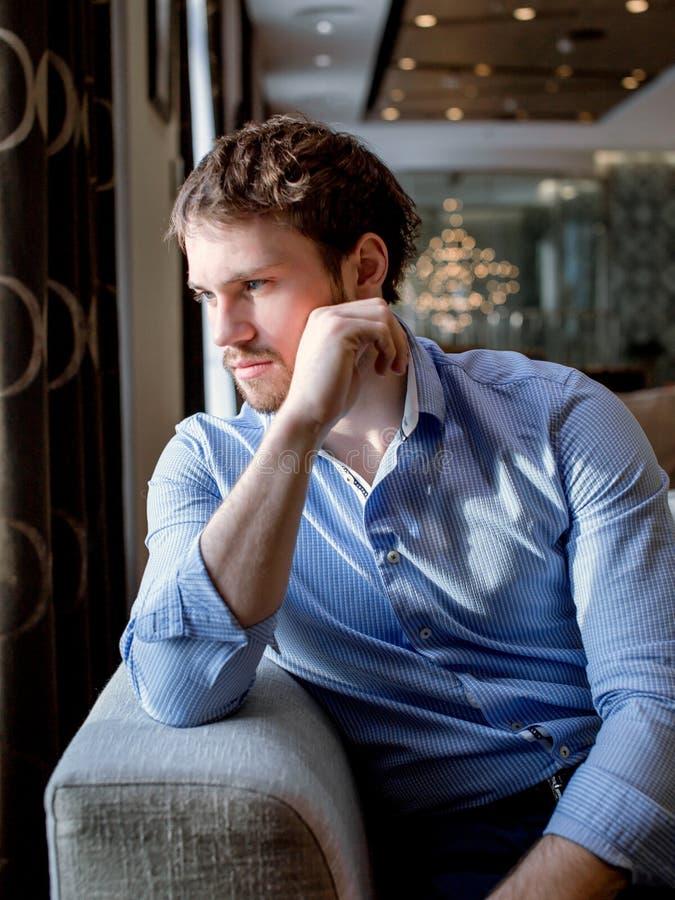 Το καυκάσιο αρσενικό με την καφετιά τρίχα αναμένει την υπηρεσία στον καναπέ στοκ φωτογραφία με δικαίωμα ελεύθερης χρήσης