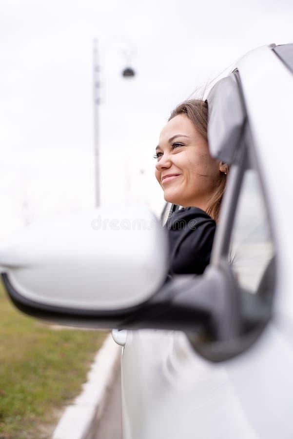 Το καυκάσιο κορίτσι κοιτάζει από το παράθυρο του μπροστινού καθίσματος επιβατών ενός άσπρου αυτοκινήτου στοκ εικόνες