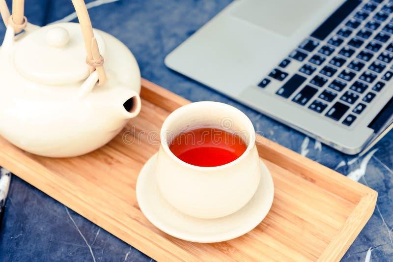 Το καυτό τσάι είναι σε ένα γυαλί σε έναν ξύλινο δίσκο κοντά στον υπολογιστή στοκ φωτογραφία με δικαίωμα ελεύθερης χρήσης