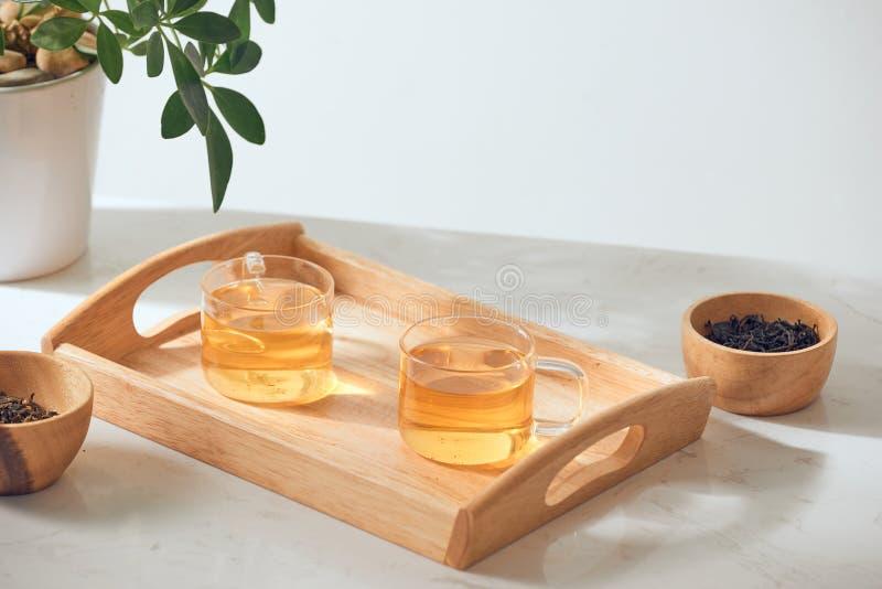 Το καυτό τσάι είναι στο γυαλί Τοποθετημένος σε έναν ξύλινο δίσκο στοκ εικόνα