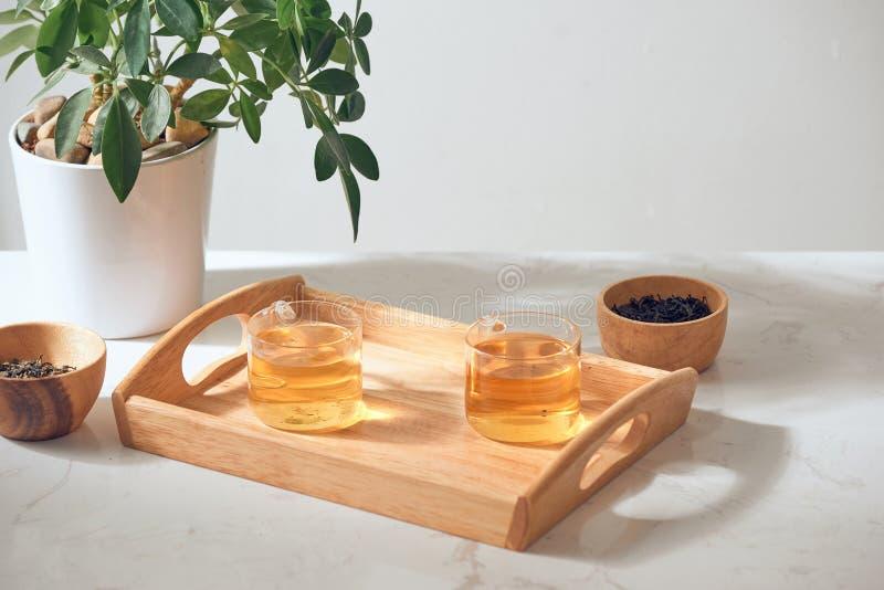 Το καυτό τσάι είναι στο γυαλί Τοποθετημένος σε έναν ξύλινο δίσκο στοκ εικόνες με δικαίωμα ελεύθερης χρήσης