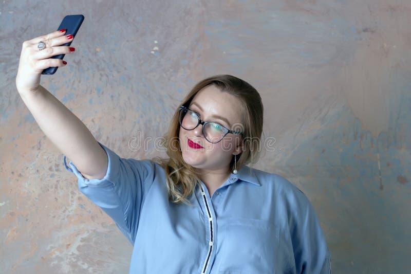 Το καφετής-μαλλιαρό κορίτσι κάνει selfie με το τηλέφωνο στοκ φωτογραφίες