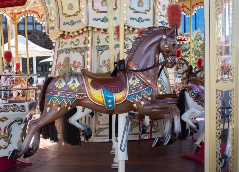 Το καφετί εκλεκτής ποιότητας διακοσμητικό άλογο καρναβαλιού σε εύθυμο πηγαίνει γύρω από το ιπποδρόμιο στον εκθεσιακό χώρο στοκ εικόνες με δικαίωμα ελεύθερης χρήσης