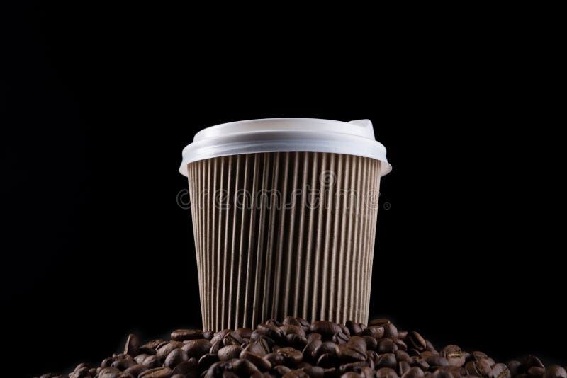 Το καφετί φλυτζάνι καφέ χαρτονιού, με ένα άσπρο καπάκι, στέκεται σε έναν σωρό των φασολιών καφέ, έννοια, σε ένα μαύρο υπόβαθρο στοκ εικόνες