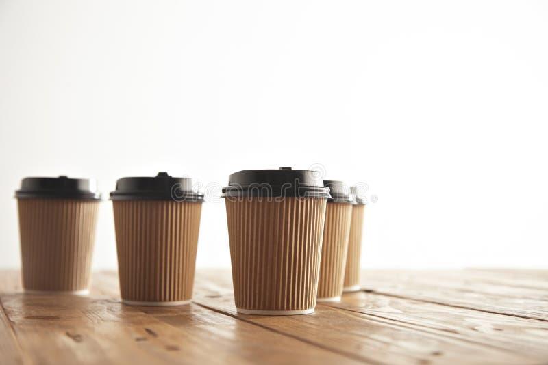 Το καφετί χαρτόνι παίρνει μαζί τα φλυτζάνια εγγράφου με τα μαύρα καλύμματα καθορισμένα στοκ φωτογραφίες
