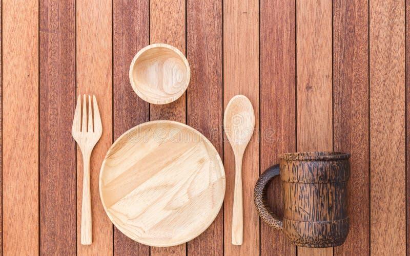 Το κενοί ξύλινοι πιάτο, το δίκρανο, το κουτάλι και ο καφές κοιλαίνουν στον ξύλινο πίνακα στοκ φωτογραφίες με δικαίωμα ελεύθερης χρήσης