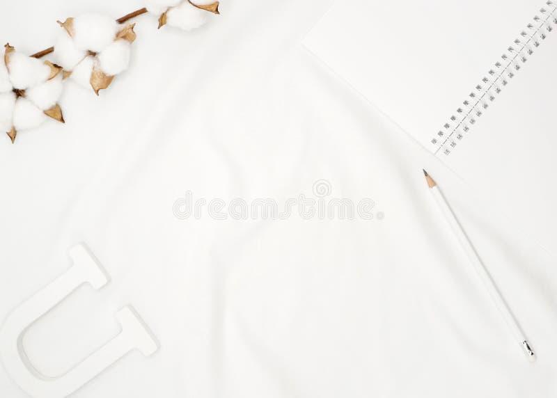 Το κενό άσπρο σπειροειδές σημειωματάριο με το μολύβι, βαμβάκι ανθίζει και ξύλινη επιστολή στο άσπρο σεντόνι στοκ εικόνες με δικαίωμα ελεύθερης χρήσης
