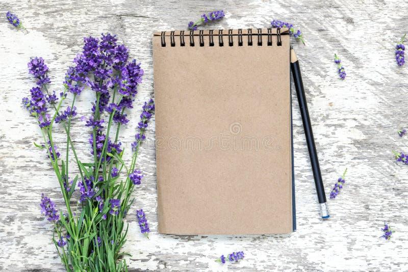 Το κενό εκλεκτής ποιότητας σημειωματάριο με lavender ανθίζει την ανθοδέσμη και το μολύβι πέρα από τον άσπρο ξύλινο πίνακα Τοπ όψη στοκ εικόνα