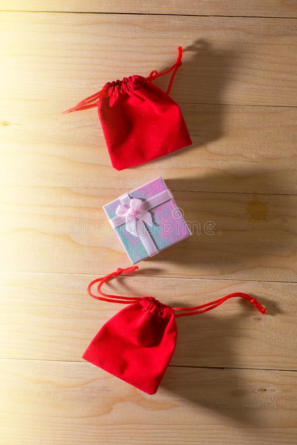 Το κιβώτιο δώρων και η κόκκινη τσάντα δώρων τύλιξαν τα Χριστούγεννα και Newyear παρουσιάζει με τα τόξα και τις κορδέλλες, υπόβαθρ στοκ εικόνες