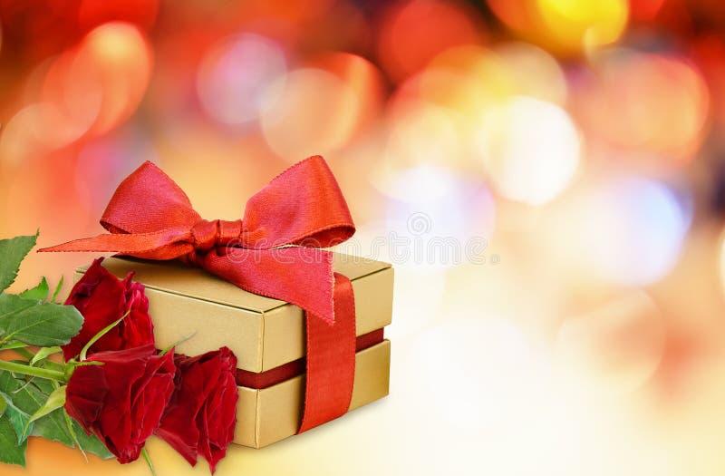 Το κιβώτιο δώρων με το κόκκινο τόξο κορδελλών και κόκκινος αυξήθηκε λουλούδια στοκ φωτογραφία με δικαίωμα ελεύθερης χρήσης