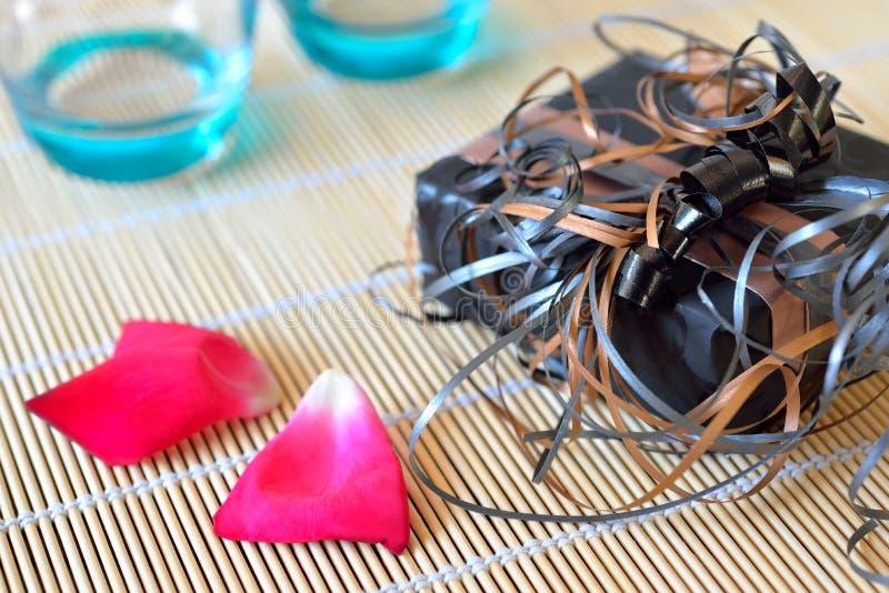 Το κιβώτιο δώρων με τις κορδέλλες αυξήθηκε πέταλα πίνοντας τα γυαλιά στοκ φωτογραφία