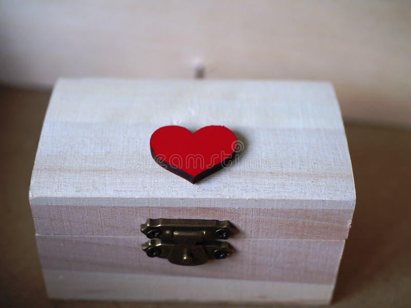 Το κιβώτιο καρδιών και δώρων, ξύλινη κασετίνα έκλεισε με μια κόκκινη καρδιά, καλή για την ημέρα του βαλεντίνου στοκ εικόνες
