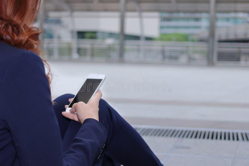 Το κινητό έξυπνο τηλέφωνο κρατιέται σε ετοιμότητα της επιχειρησιακής γυναίκας στη διάβαση πεζών ενάντια στο διάστημα αντιγράφων σ στοκ φωτογραφία