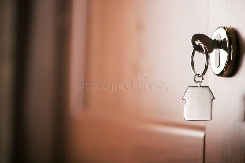 Το κλειδί σπιτιών σε ένα σπίτι διαμόρφωσε το ασημένιο μπρελόκ στην κλειδαριά ενός entr στοκ εικόνες