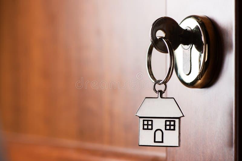 Το κλειδί σπιτιών σε ένα σπίτι διαμόρφωσε το ασημένιο μπρελόκ στην κλειδαριά μιας πόρτας εισόδων στοκ φωτογραφία