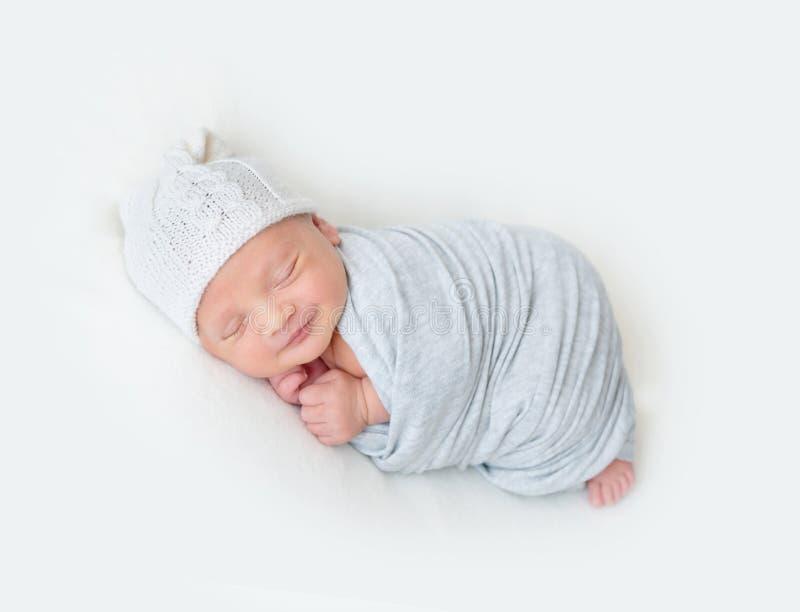 Το κοισμένος νεογέννητο μωρό σε ένα ανοικτό μπλε περικάλυμμα στοκ εικόνες