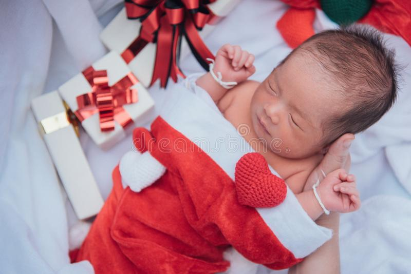 Το κοισμένος νεογέννητο μωρό στη μητέρα παραδίδει το καπέλο Χριστουγέννων με το κιβώτιο δώρων από Άγιο Βασίλη και την καρδιά νημά στοκ φωτογραφίες