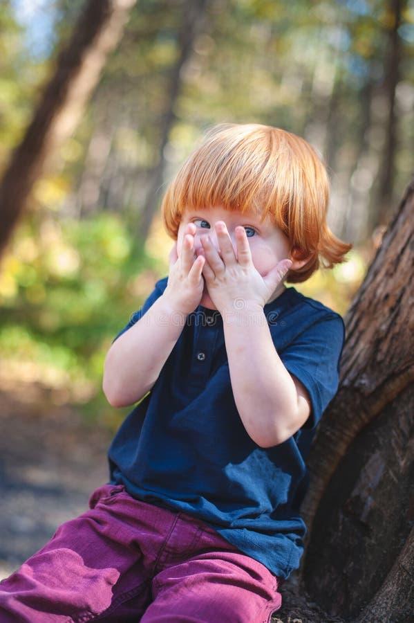 Το κοκκινομάλλες αγόρι καλύπτει το πρόσωπό του στοκ φωτογραφία με δικαίωμα ελεύθερης χρήσης