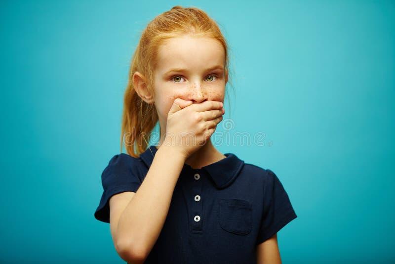 Το κοκκινομάλλες κορίτσι κάλυψε το στόμα της με το χέρι και εξετάζει τη κάμερα με την ανησυχία σχετικά με το απομονωμένο μπλε υπό στοκ φωτογραφία
