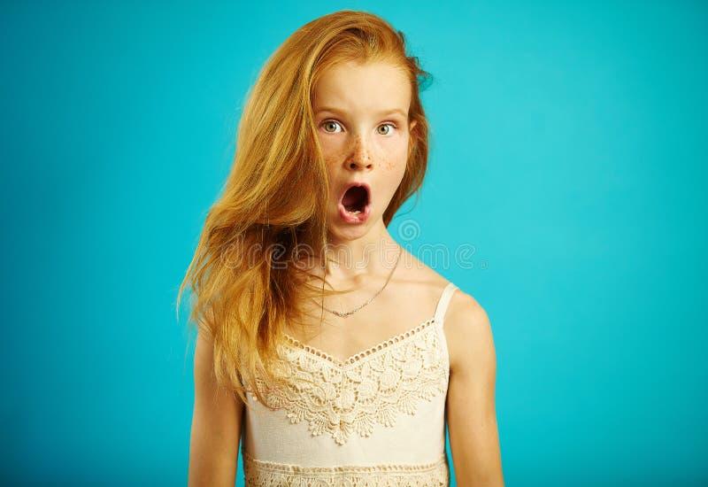Το κοκκινομάλλες κορίτσι στο άσπρο φόρεμα με την έκπληκτη έκφραση ανοίγει το στόμα της και τα μάτια ευρέως, παρουσιάζουν ισχυρή σ στοκ εικόνα με δικαίωμα ελεύθερης χρήσης
