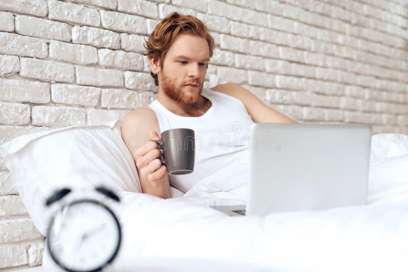 Το κοκκινομάλλες awakining άτομο βρίσκεται στο κρεβάτι με το lap-top στοκ εικόνα