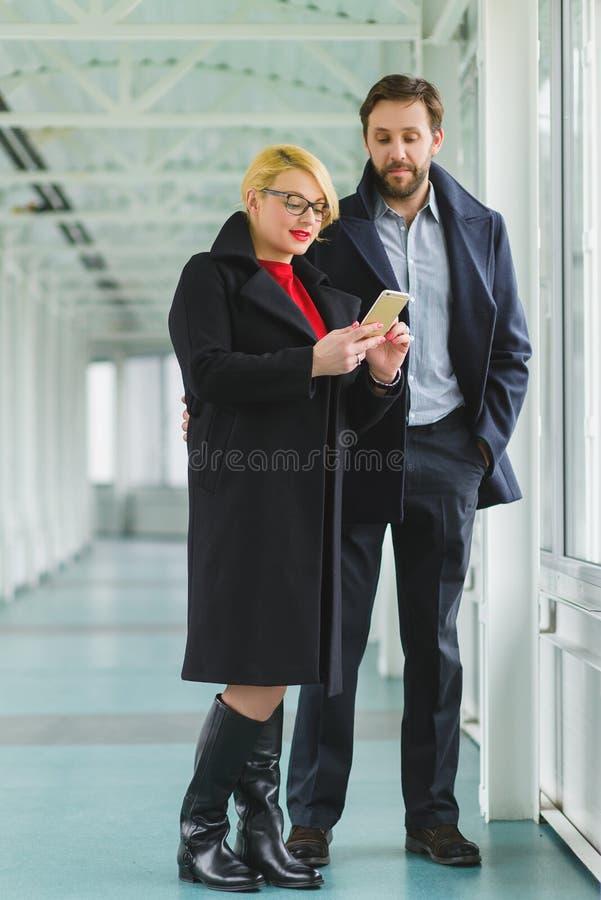 Το κομψό ζεύγος έντυσε στο παλτό εξετάζοντας στο έξυπνο τηλέφωνο το λόμπι στοκ εικόνες με δικαίωμα ελεύθερης χρήσης