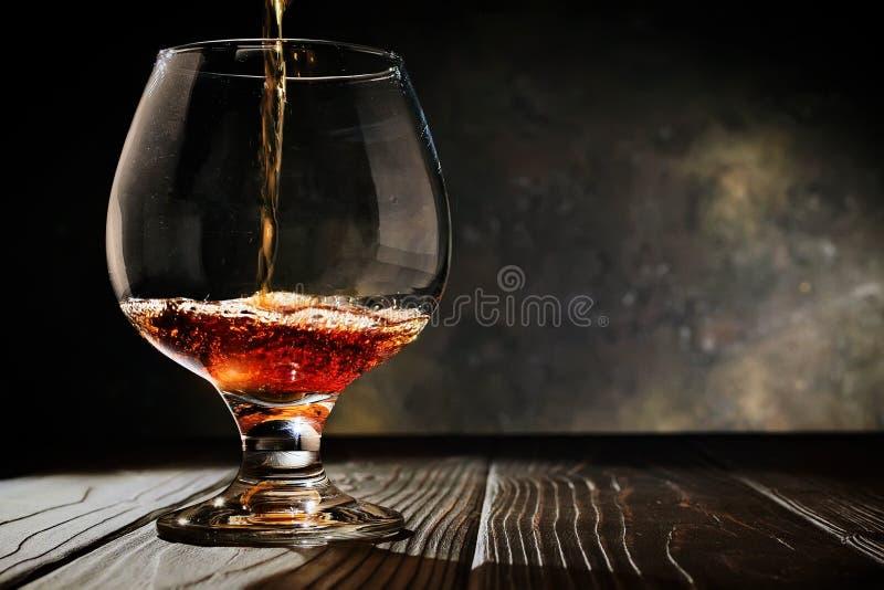 Το κονιάκ χύνεται σε ένα γυαλί σε ένα παλαιό σκοτεινό ξύλινο υπόβαθρο Ελεύθερο διάστημα αντιγράφων Εκλεκτική εστίαση στοκ εικόνες με δικαίωμα ελεύθερης χρήσης