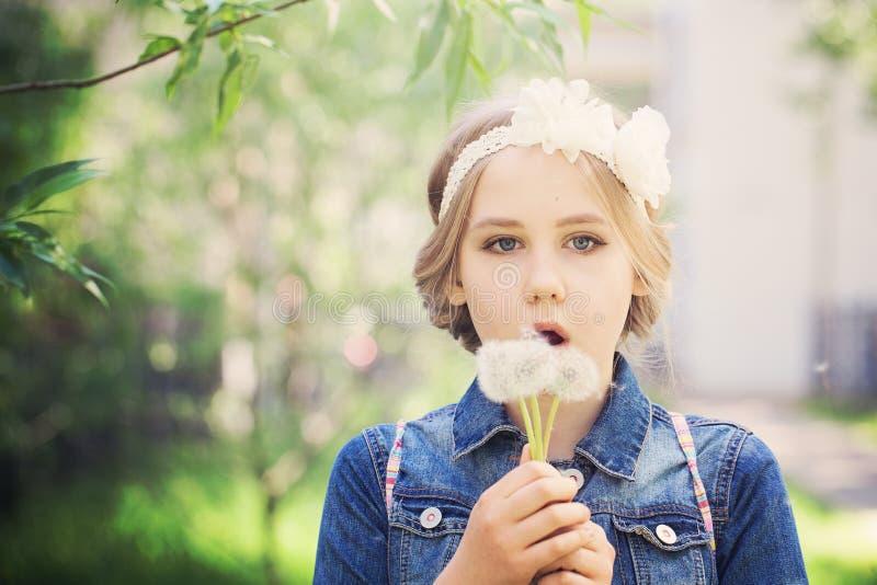 Το κορίτσι άνοιξη με μια πικραλίδα ανθίζει στοκ εικόνες