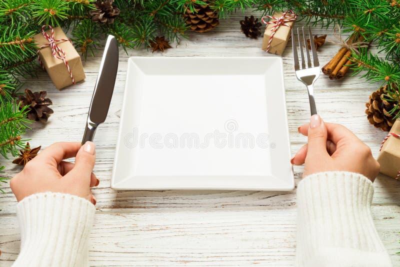 Το κορίτσι άποψης προοπτικής κρατά το δίκρανο και το μαχαίρι διαθέσιμα και είναι έτοιμο να φάει Κενό άσπρο τετραγωνικό πιάτο στο  στοκ φωτογραφίες με δικαίωμα ελεύθερης χρήσης