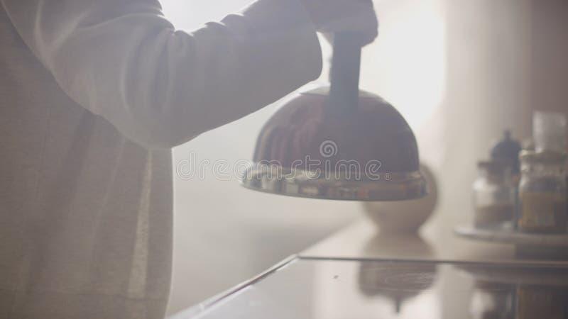 Το κορίτσι έβαλε την μπλε κατσαρόλα σε μια σόμπα αερίου κουζινών Σφυρίζοντας κατσαρόλα Stovetop υπό εξέταση στοκ εικόνα