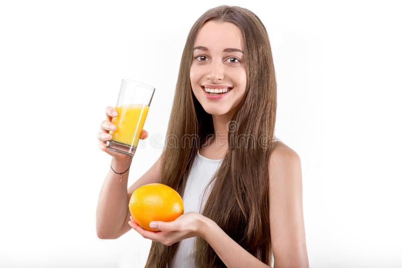 Το κορίτσι έντυσε σε ένα άσπρο πουκάμισο πίνοντας το χυμό από πορτοκάλι ενάντια σε ένα wh στοκ εικόνα