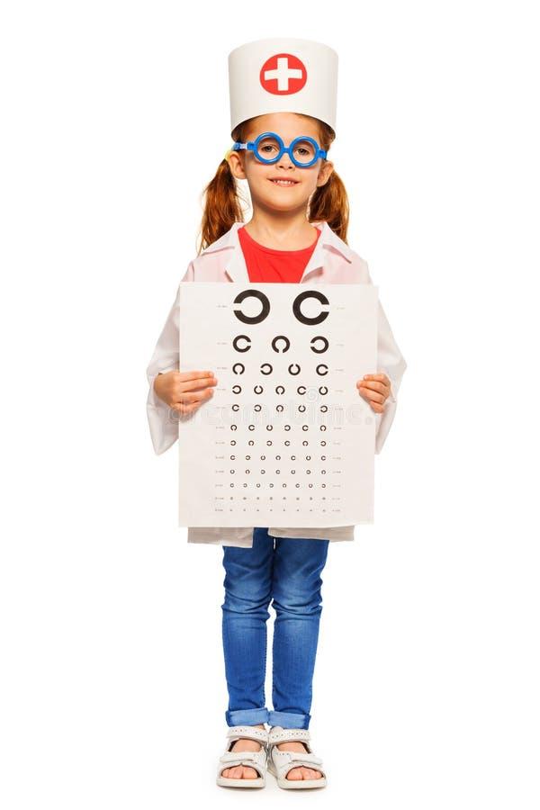 Το κορίτσι έντυσε στο κοστούμι και την ΚΑΠ του οφθαλμολόγου στοκ φωτογραφία