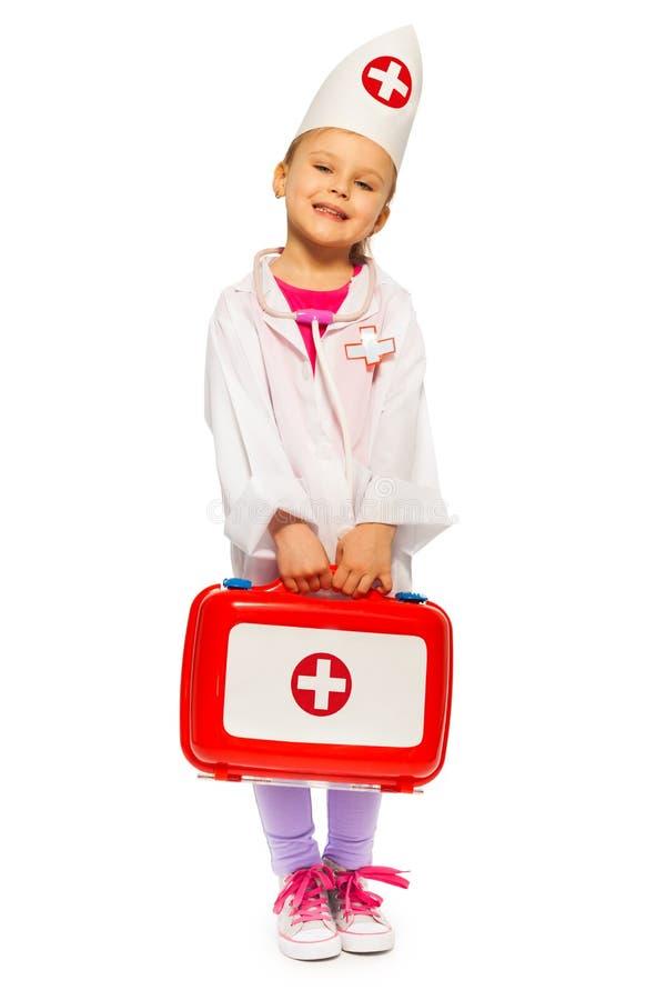 Το κορίτσι έντυσε όπως έναν γιατρό με την εξάρτηση πρώτων βοηθειών παιχνιδιών στοκ εικόνα