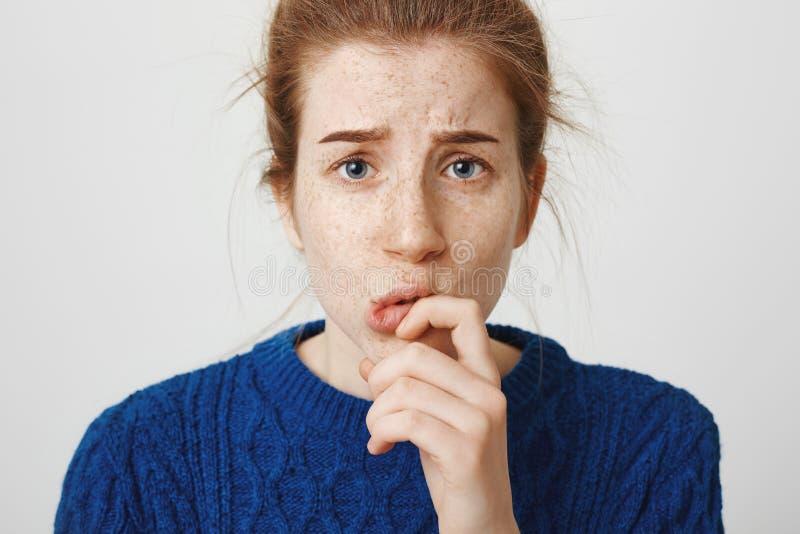 Το κορίτσι έχει τις αμφιβολίες και unconfident σε την Ανησυχημένα ελκυστικά redhead θηλυκά συνοφρύωμα, και κράτημα στοκ εικόνες