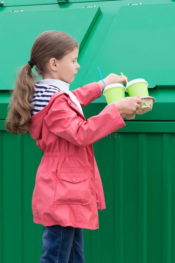 Το κορίτσι ήρθε για να ρίξει γυαλιά στο σκουπιδοτενεκέ στοκ φωτογραφία