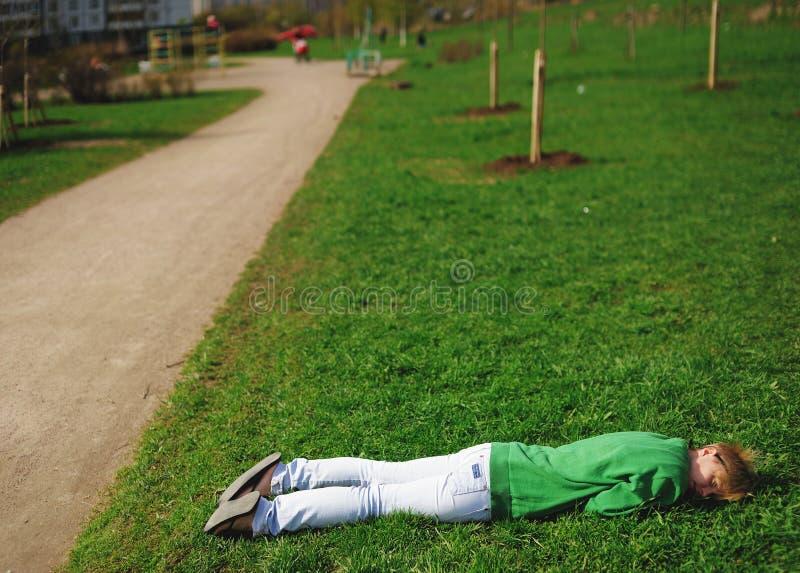 Το κορίτσι ήταν κουρασμένο και καθορίζει για να χαλαρώσει στη χλόη κοντά στο δρόμο στοκ φωτογραφία με δικαίωμα ελεύθερης χρήσης