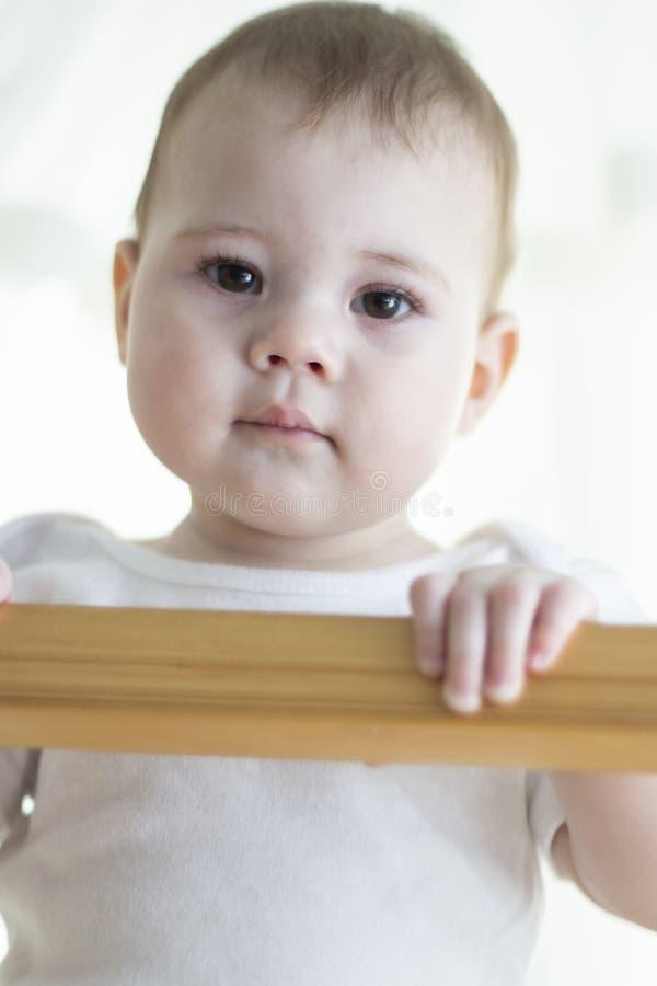 Το κορίτσι αγοράκι με το λευκό κοιτάζει από το παχνί κάτω Πορτρέτο μιας κινηματογράφησης σε πρώτο πλάνο παιδιών : Χαριτωμένα καφε στοκ φωτογραφία